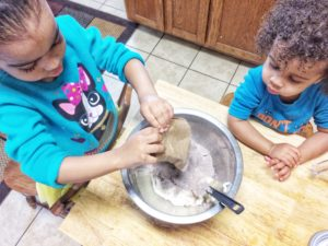 Kid baking Valentine's Day cupcakes, chocolate pudding cream cheese frosting